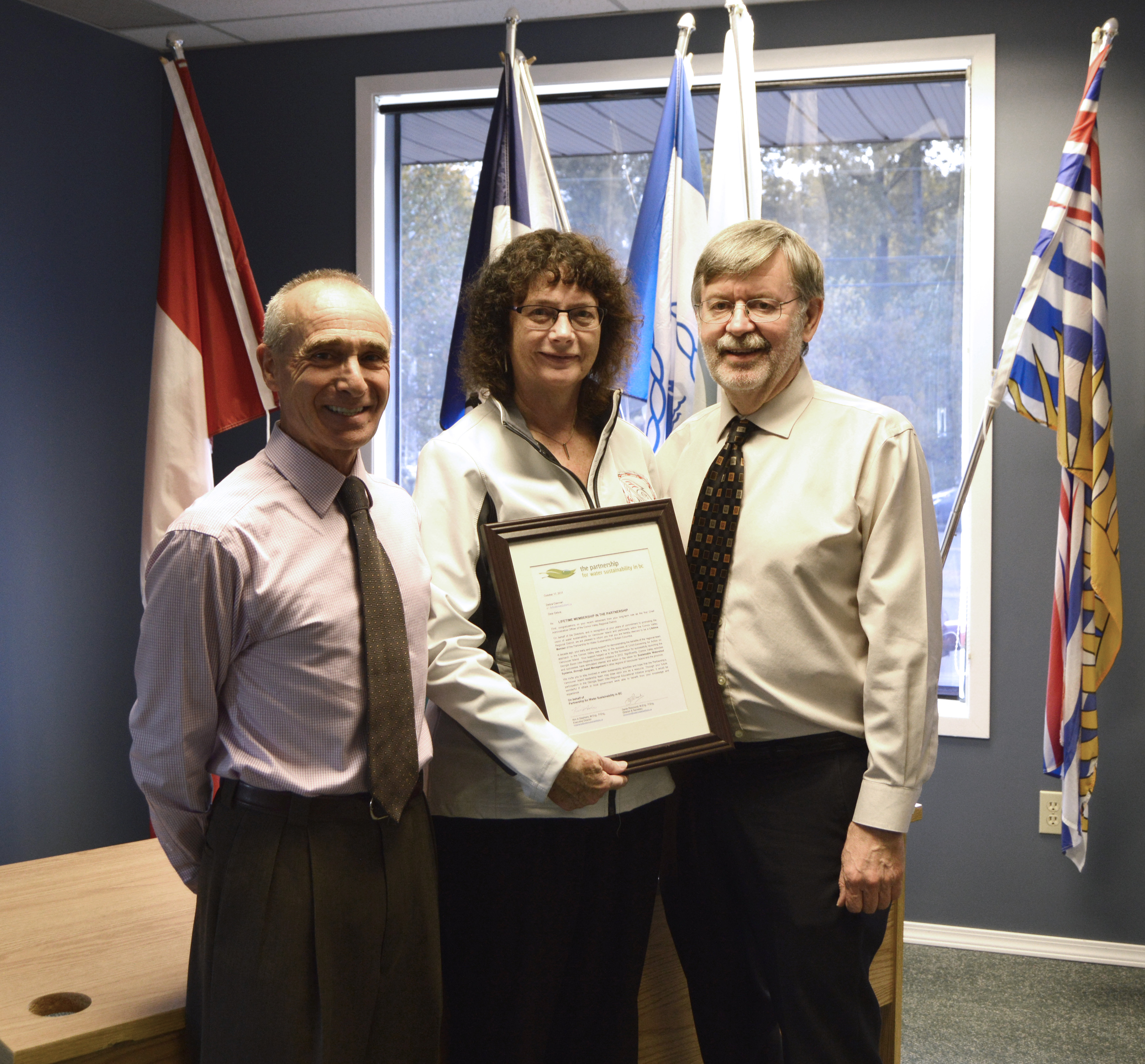 """Derek Richmond (Director & CAVI Past-Chair) and Kim Stephens (Executive Director) co-presented a framed copy of the """"letter of recognition"""" attesting to Debra's Lifetime Membership in the Partnership."""