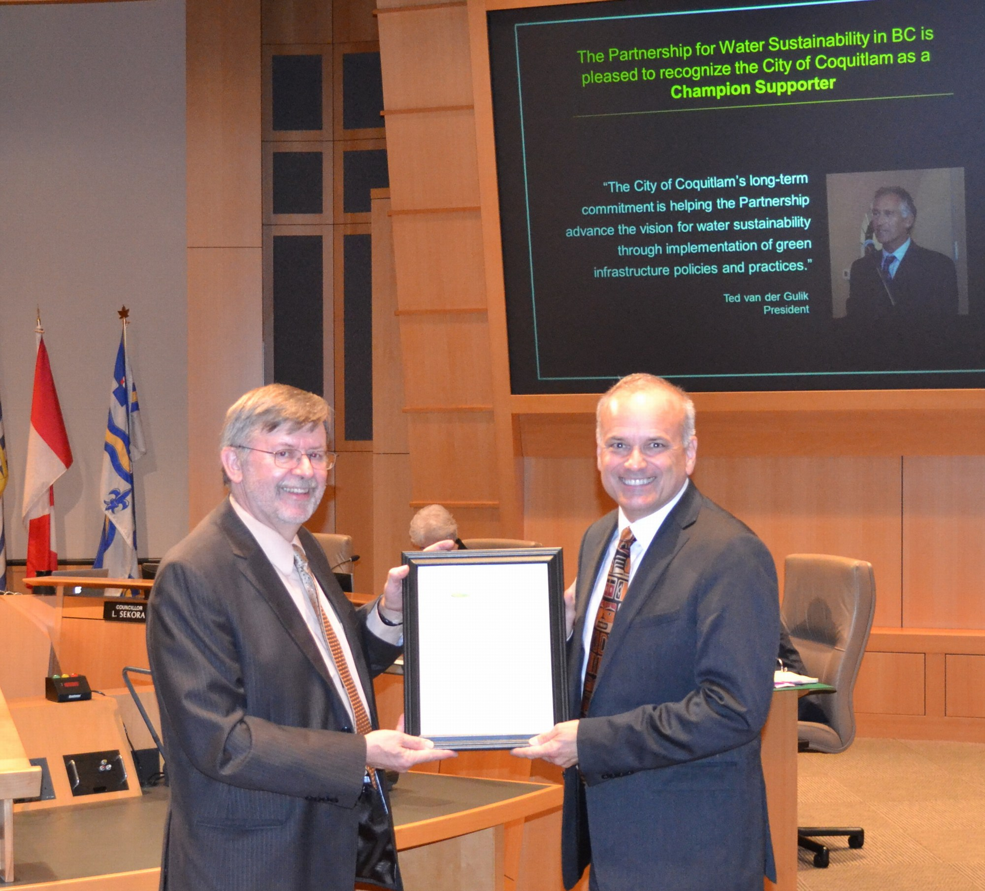 "Kim Stephens (L) presents framed ""letter of recognition"" to Mayor Richard Stewart (R)"