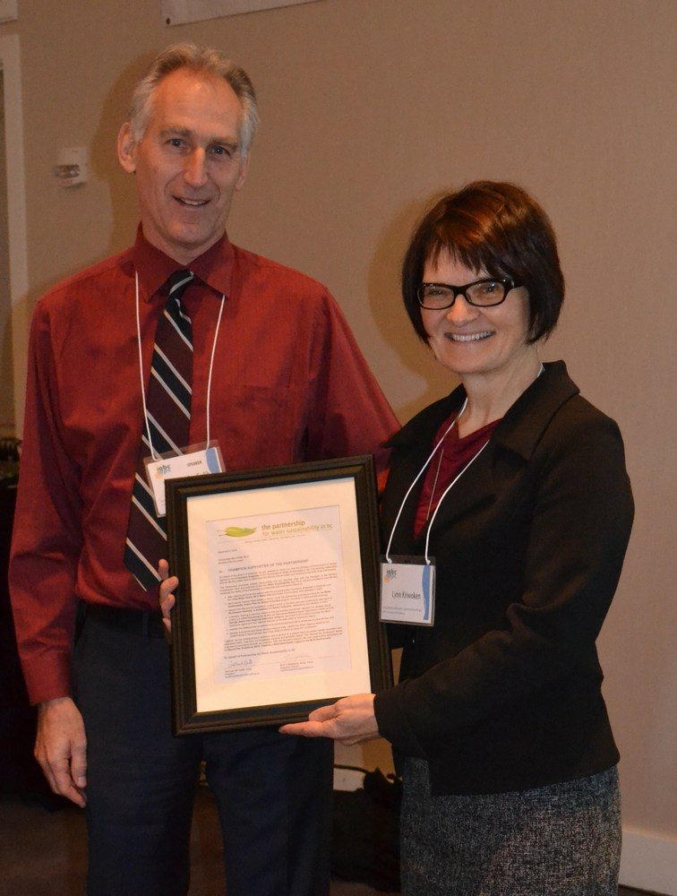 """Ted van der Gulik (L), President of the Partnership for Water Sustainability in BC, presented the framed """"Champion Supporter recognition"""" to Lynn Kriwoken (R), Executive Director in the BC Ministry of Environment"""