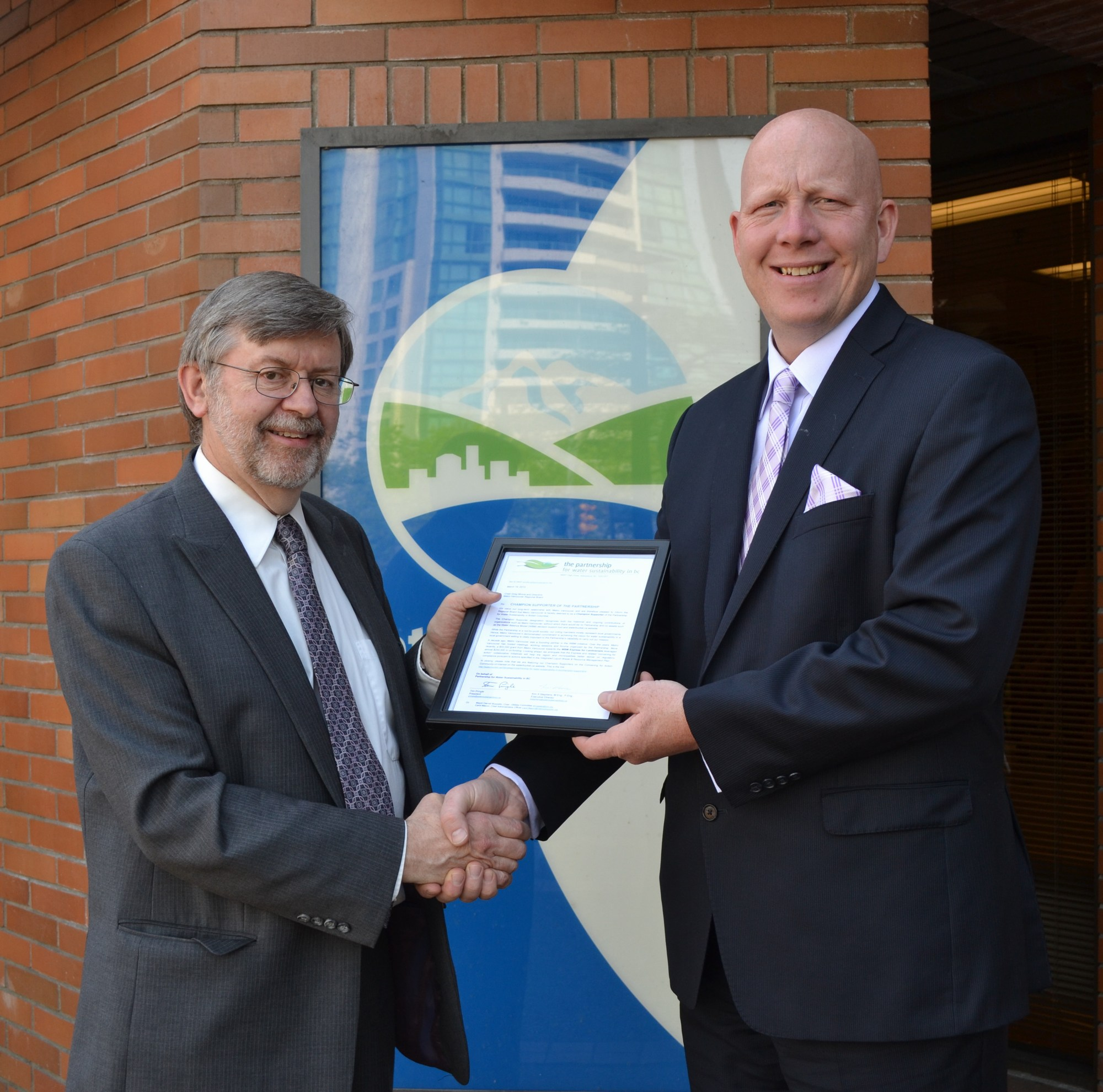 "Kim Stephens (L), Executive Director of the Partnership for Water Sustainability, presents the ""letter of recognition"" to Metro Vancouver Chair Greg Moore (R) in May 2014"